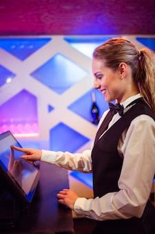 Barista sorridente mentre si utilizza il moderno registratore di cassa