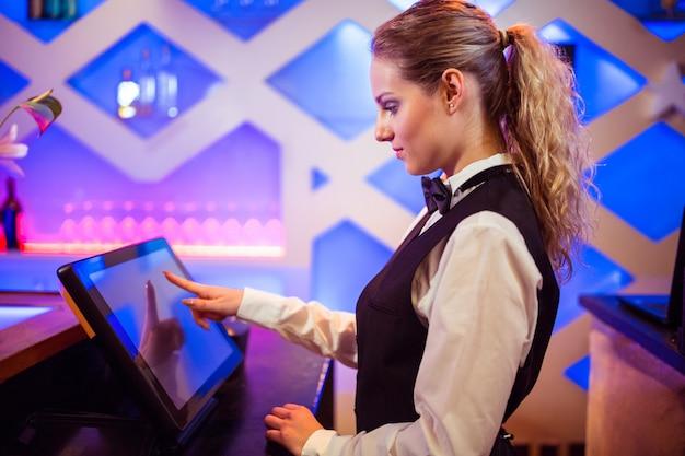 Barista utilizzando il moderno registratore di cassa al bancone del bar