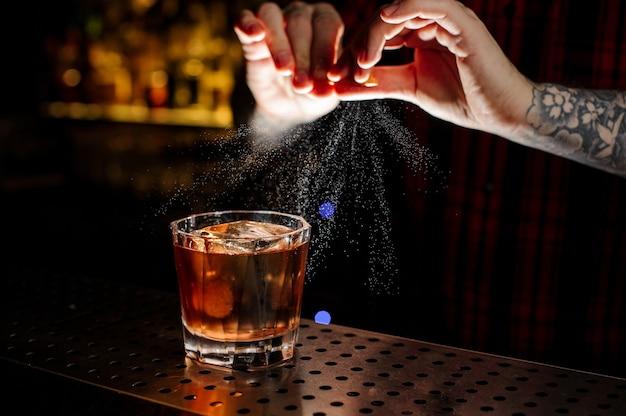Barman che aggiunge succo di scorza d'arancia a un cocktail della legione straniera nel bicchiere sul bancone del bar