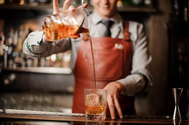 Barman in bar interno rendendo alcolici cocktail.