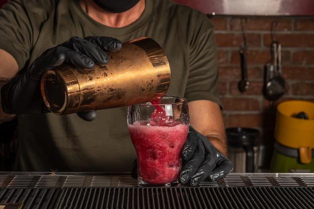 Barman al bar che versa cocktail alcolico rosso in un bicchiere