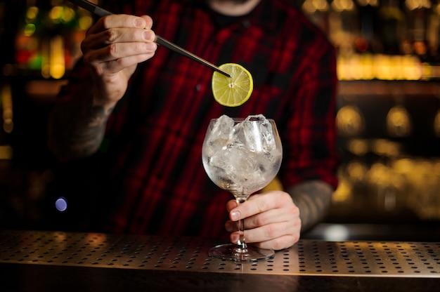 Barman che decora cocktail aspro fresco con una fetta di lime e cubetti di ghiaccio sulla barra
