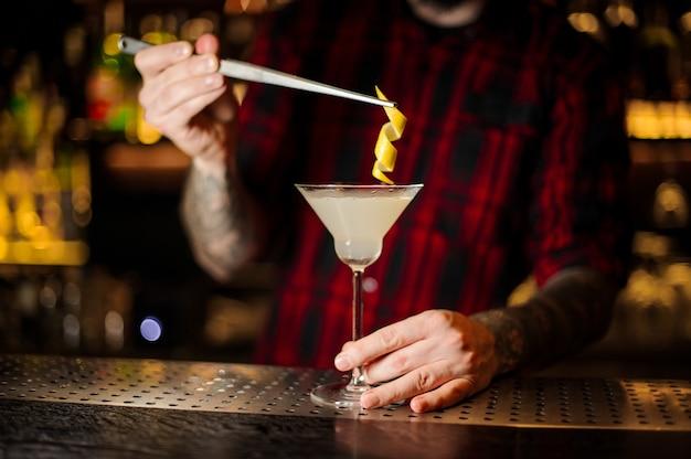 Barman che decora cocktail alcolico fresco aspro e dolce con una buccia d'arancia sulla barra
