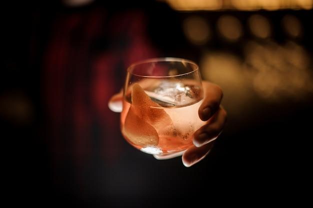 Barman mano che tiene whisky dof bicchiere di fresco capitano james cook cocktail