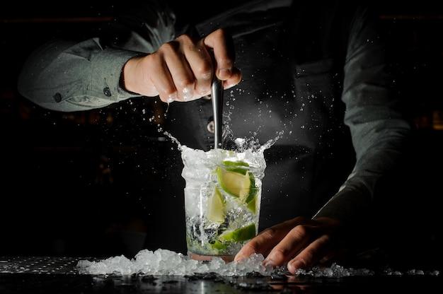 Mano del barista che spreme il succo fresco dalla calce che produce il cocktail di caipirinha