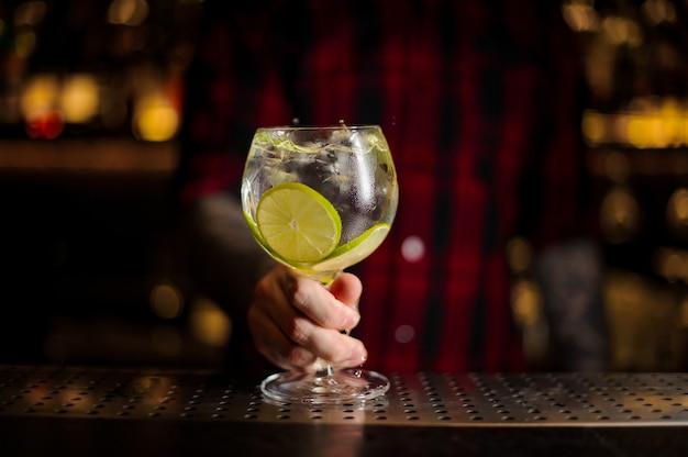 Barman che tiene un bicchiere da cocktail con bevanda fresca di agrumi aspro e dolce con fette di lime