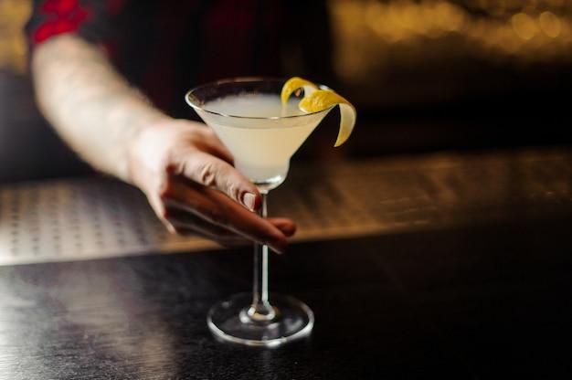 Barman che tiene un bicchiere di cocktail fresco acido e dolce decorato con buccia d'arancia sul bancone del bar