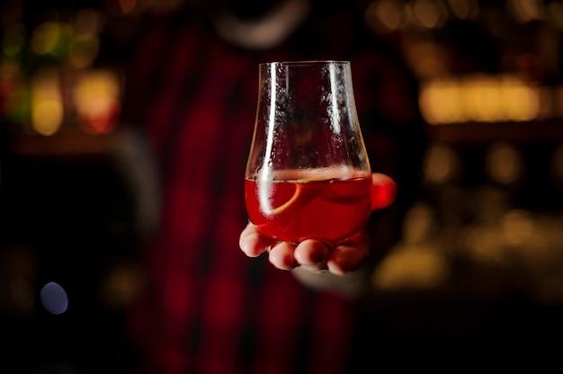 Barman che tiene un bicchiere di cocktail rosso gustoso fresco e dolce con una fetta di buccia d'arancia