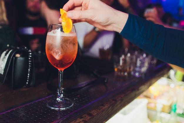 Barman che prepara cocktail con spumante, aperol e arancia. primo piano vista focalizzata sulle mani.