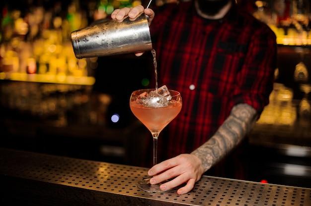 Barman che versa cocktail alcolico in un bicchiere pieno di cubetti di ghiaccio sul bancone del bar