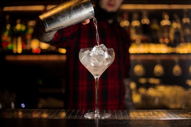 Barman versando la bevanda alcolica fresca dallo shaker in un bicchiere con cubetti di ghiaccio contro le luci