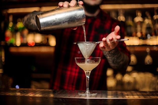 Barman che versa cocktail alcolico succoso fresco e dolce dallo shaker nel bicchiere da cocktail usando il colino sulla barra