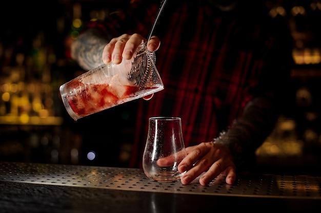 Barman che versa cocktail rosso agrodolce fresco e gustoso in un bicchiere da cocktail vuoto sulla barra