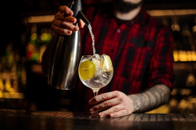 Barman versando la soda in un bicchiere da cocktail con bevanda alcolica e lime sul bancone del bar