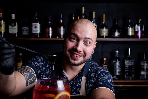 Il barista mette nel bicchiere della fresca e gustosa siringa aperol cocktail peace of ice.