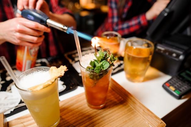 Il barista dà fuoco a un rametto di menta su cocktail di colore arancione
