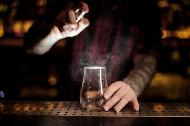 Barman che spruzza l'amaro in un bicchiere da cocktail basso e vuoto sul bancone del bar contro le luci