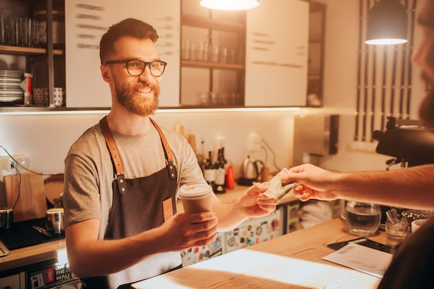 Barman in piedi dietro il bancone del bar e con in mano una tazza di caffè che ha fatto per il cliente. il barista sembra felice e sorridente mentre riceve un denaro per l'ordine dal cliente.