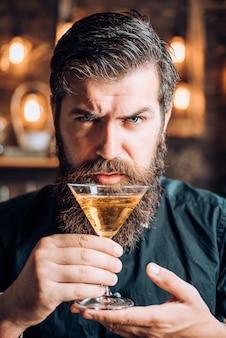 Barman con martini o liquore. uomo barbuto che indossa tuta e bere alcolici. bere e celebrazione concetto di festa. degustazione e degustazione.