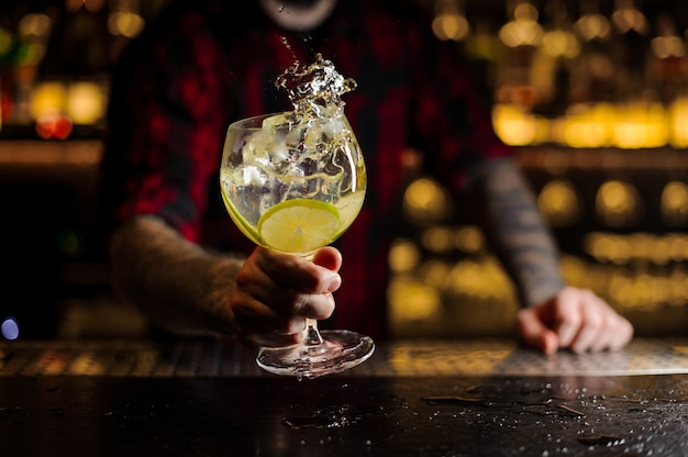 Barman con tatuaggi che tiene un bicchiere da cocktail con bevanda fresca di agrumi aspro e dolce con fette di lime