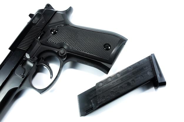 La canna di una pistola nera e di una rivista, la pistola si trova su uno sfondo bianco. avvicinamento.