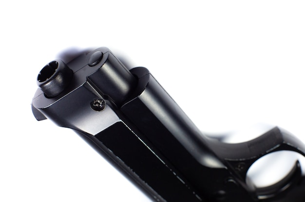La canna di una pistola nera, la pistola si trova su uno sfondo bianco. avvicinamento.