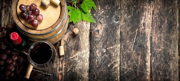 Botte di vino rosso con uva e un cavatappi. su uno sfondo di legno.