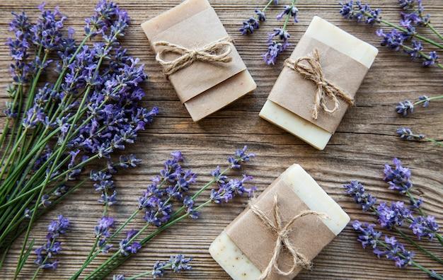 Barre di sapone fatto a mano con fiori di lavanda su sfondo grunge di legno.