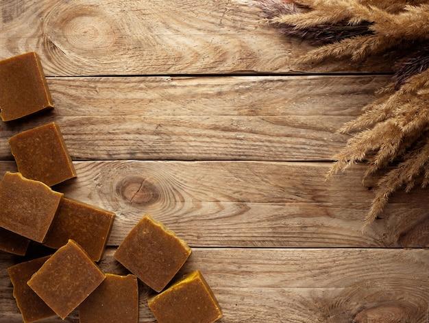 Barre di sapone naturale con fiori secchi su un tavolo di legno.