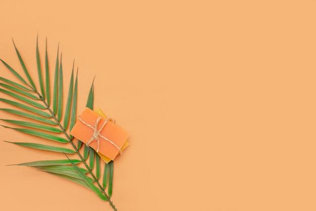 Saponette solide legate con spago con foglia di palma su fondo beige. cosmetici naturali ecologici.