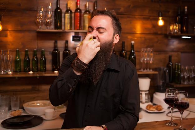 Bartende che mangia una deliziosa mela verde dietro il bancone del bar. uomo alla moda.