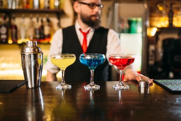 Il barista dietro il bancone del bar mostra cocktail alcolici