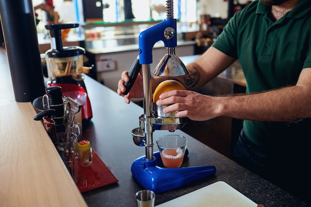 Il barista barista prepara il succo appena spremuto sulla macchina