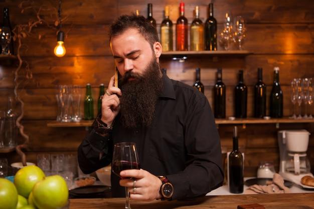 Barista dietro il bancone gustando un bicchiere di vino e parlando al telefono.