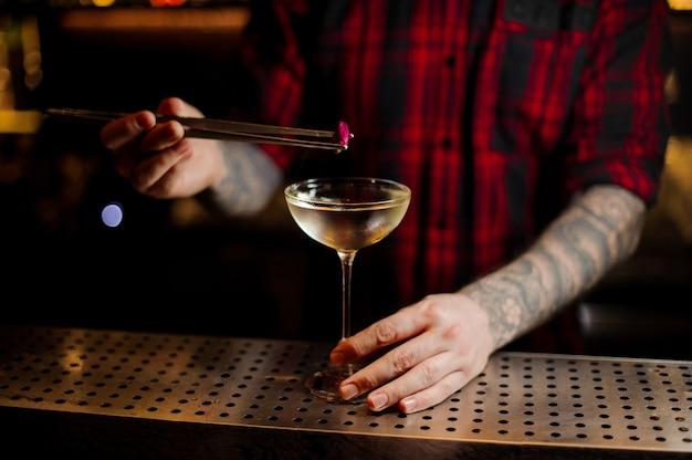 Barista che decora l'elegante cocktail con un piccolo bocciolo di rosa rosa sul bancone del bar