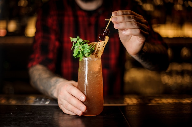 Barista che decora un bicchiere alto riempito con cocktail cobras fang fresco