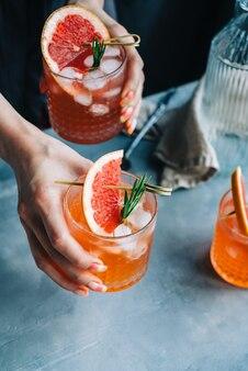 Barista mano che tiene bicchieri di limonata cocktail pompelmo con ghiaccio e rosmarino.