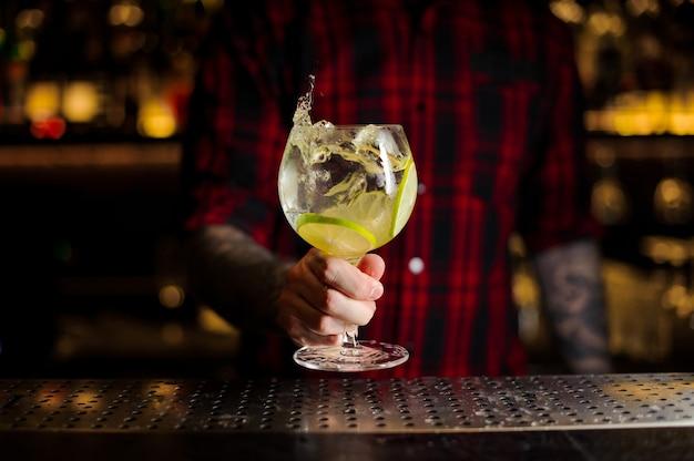 Barista che tiene un bicchiere da cocktail con bevanda fresca di agrumi aspro e dolce con fette di lime
