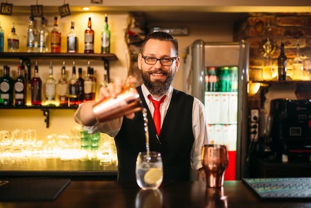 Il barista sta preparando un cocktail alcolico al bancone