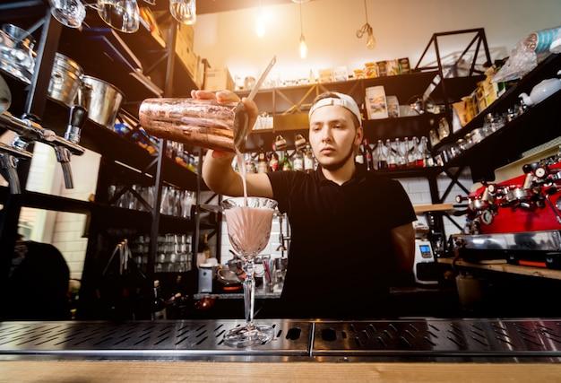 Il barista sta preparando un cocktail al bancone del bar. cocktail freschi. barman al lavoro. ristorante. vita notturna.