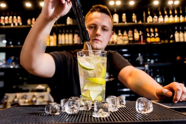 Il barista sta preparando un cocktail al bancone del bar. cocktail freschi. barman al lavoro.