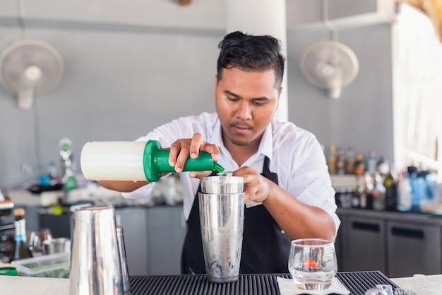Il barista sta preparando un cocktail al bancone del bar.