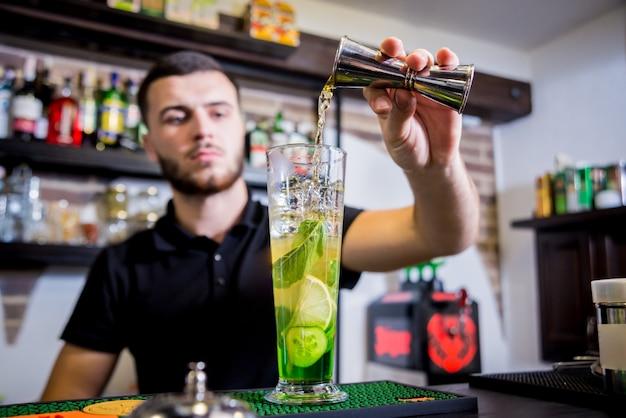 Il barista sta preparando un cocktail analcolico al bancone del bar. cocktail freschi. barman al lavoro. ristorante. vita notturna.