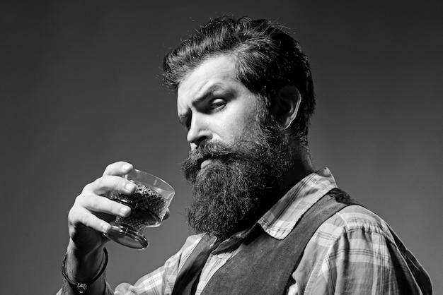 Grembiule in pelle da barista che tiene cocktail di whisky in vetro. bere alcol