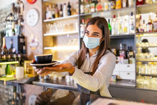 Il barista in maschera medica serve caffè latte al bancone durante la pandemia di coronavirus