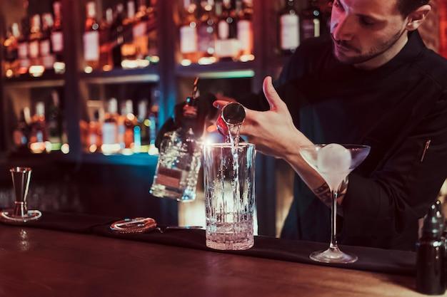 Barista cocktail di miscelazione. indossa un costume nero. è in un pub. uomo barbuto.