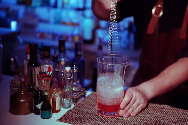 Il barista ha rifiutato il cocktail in una tazza di vetro. immagine virata con toni blu-gialli.