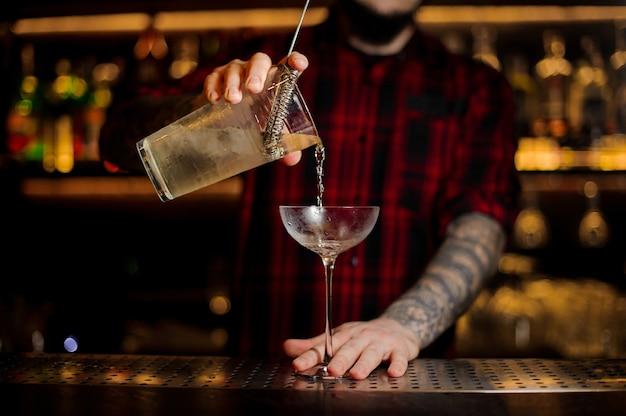 Barista che versa cocktail alcolico in un bicchiere vuoto sul bancone del bar contro le luci
