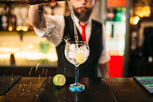Barista versando bevanda alcolica in vetro