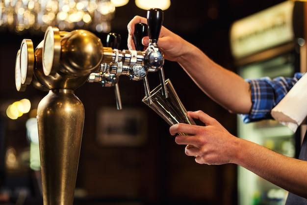 Barista che versa la birra fresca nel pub, mano del barista al rubinetto della birra che versa una birra chiara alla spina, birra dal rubinetto, bicchiere da riempire con birra, birra fresca, pub.bar.ristorante.european bar. american bar.